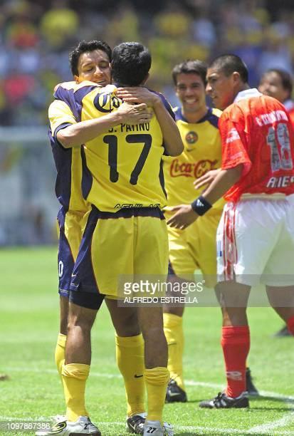 Christian Patiño of the America de Mexico team hugs teammate Hugo Castillo who scored the second goal during the Copa Libertadores competition...