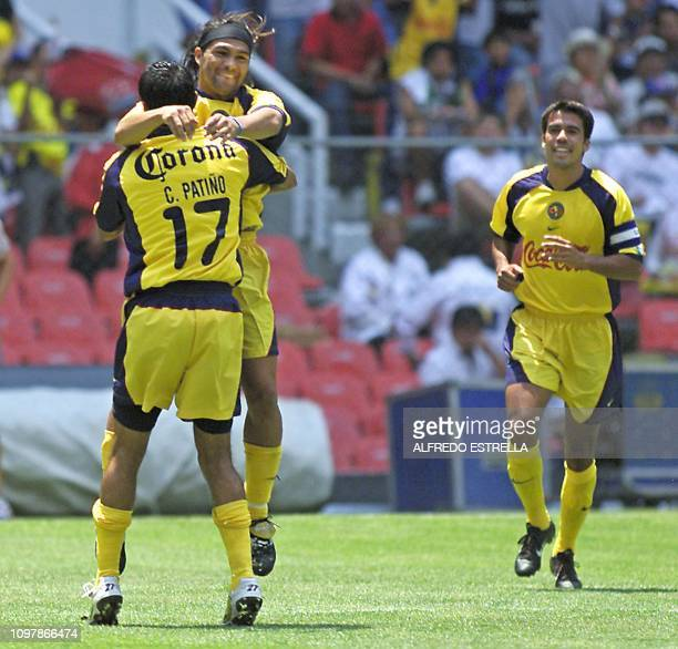 Christian Patiño of the America de Mexico team hugs teammate Reinaldo Navia who scored the first goal during the Copa Libertadores game against...