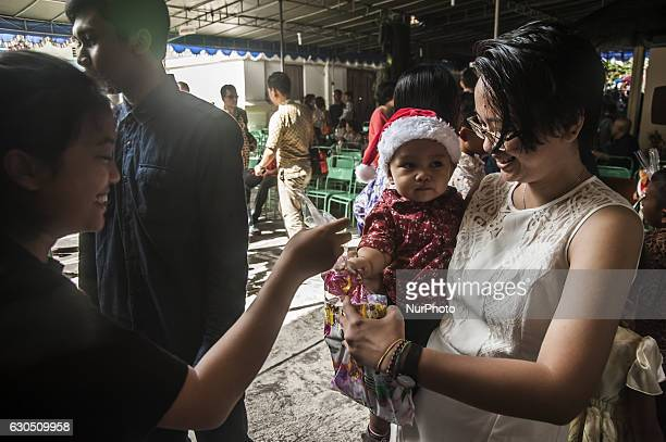 Christian people give a gift to a child when attend mass in celebration of Christmas in Sacred Heart of Jesus Catholic Church in Yogyakarta Indonesia...