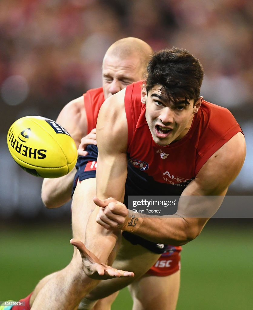 Christian Petracca of the Demons handballs whilst being tackled by Zak Jones of the Swans during the round 15 AFL match between the Melbourne Demons and the Sydney Swans at Melbourne Cricket Ground on June 30, 2017 in Melbourne, Australia.