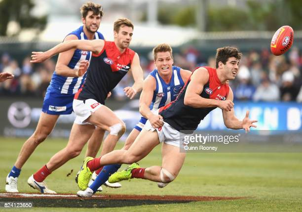 Christian Petracca of the Demons handballs whilst being tackled by Andrew Swallow of the Kangaroos during the round 19 AFL match between the North...