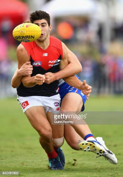 Christian Petracca of the Demons handballs whilst being tackled during the 2017 JLT Community Series match between the Western Bulldogs and the...