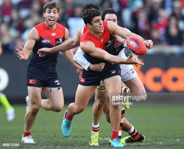Christian Petracca of the Demons handballs whilst being tackled during the round 15 AFL match between the Melbourne Demons and the St Kilda Saints at...