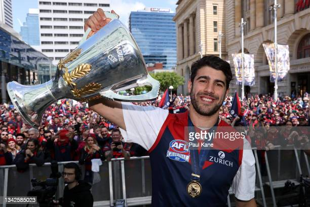 """Christian Petracca of the Demons holds the 2021 AFL Premiership Cup aloft on stage at Forrest Place """"Footy Place"""" on September 26, 2021 in Perth,..."""