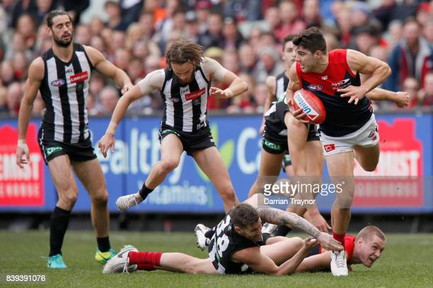 Christian Petracca of the Demons leaps over team mate during the round 23 AFL match between the Collingwood Magpies and the Melbourne Demons at...