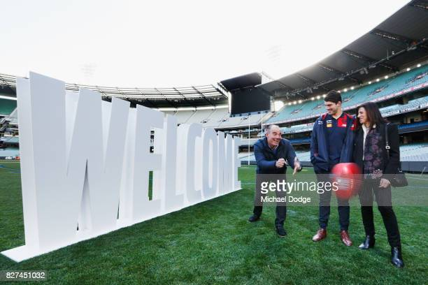 Christian Petracca watches his dad Tony handpass the ball with mum Elvira during the Melbourne Demons AFL Welcome Game Launch media opportunity at...