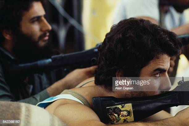 Christian Phalange militia member takes up aim on a target from a window during fighting in Beirut. The Christian Phalange are armed by and allied to...