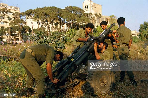 Christian Phalangist militiamen dismantle an artillery piece in the predominantly Christian East Beirut as they move heavy equipment and artillery...
