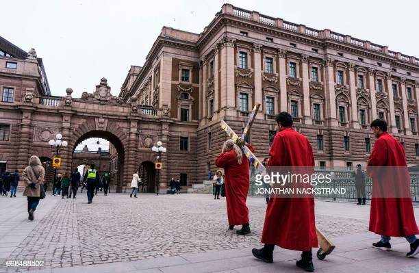 A Christian pilgrim carries a wooden cross along the Riksdagen Swedish Parliament in Stockholm Sweden during the Good Friday procession on April 14...
