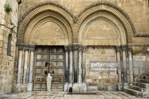 Christian pilgrim dressed as Jesus Christ stands in front of the closed door of the Holy Sepulchre Church in Jerusalem's Old City on April 10 marking...