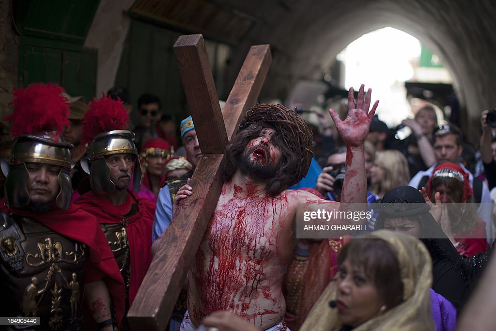 A Christian pilgrim reenacts the crucifixion of Jesus Christ along the path where Jesus walked, now known as the 'Via Dolorosa', or the 'Way of Suffering', on Good Friday in Jerusalem's Old City on March 29, 2013. Christian pilgrims mark the anniversary every year by walking from the Garden of Gethsemane on the Mount of Olives to the Church of the Holy Sepulchre in the middle of the Old City, an ancient sprawling shrine which Orthodox and Catholic Christians believe was built on the original site of the crucifixion and burial of Jesus.