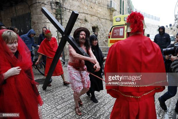 A Christian pilgrim reenacts the Passion of Christ along the Via Dolorosa during a procession marking Good Friday in Jerusalems Old City on March 30...