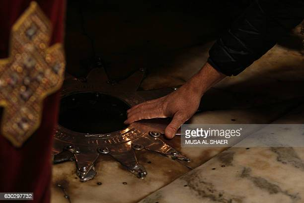 A Christian pilgrim touches a 14point silver star on the marble floor of the Grotto in the Church of the Nativity believed to be the birthplace of...