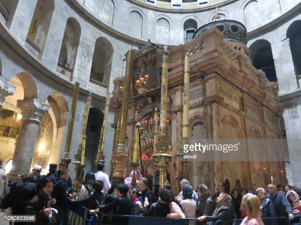 christian pilgrims are praying in church of the holy sepulchre in jerusalem old city - chiesa del santo sepolcro foto e immagini stock