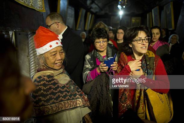 Christian pilgrims are seen at the Grotto in the Church of the Nativity on December 25 2016 in Bethlehem West Bank Every Christmas pilgrims travel to...