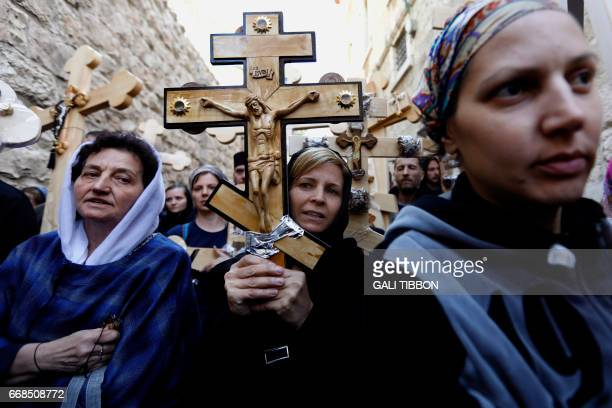 """Christian pilgrims carry wooden crosses along the path where Jesus walked, now known as the """"Via Dolorosa"""", or the """"Way of Suffering"""", on Good Friday..."""