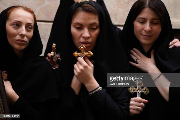Christian pilgrims carry wooden crosses along the path where Jesus walked now known as the Via Dolorosa or the Way of Suffering on Good Friday in...