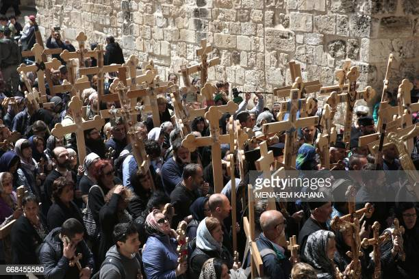 Christian pilgrims carry wooden crosses as they enter the Church of the Holy Sepulchre in Jerusalems Old City during the Good Friday celebrations on...