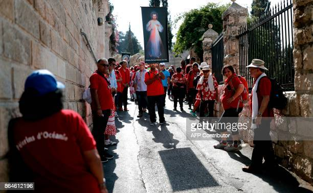 Christian pilgrims from French Polynesia walk near the Church of All Nations in the Garden of Gethsemane situated on the Mount of Olives before...