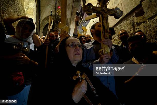 Christian pilgrims holding religious icons and wooden crosses in the Church of Holy Sepulchre during a Good Friday procession in the old city East...
