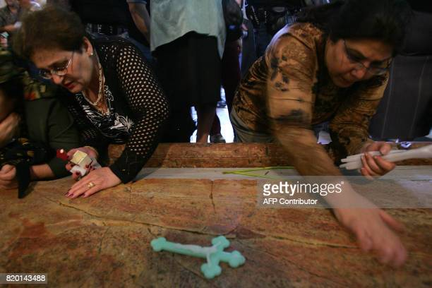 Christian pilgrims place crucifixes on the large marble slab traditionally believed to be the stone that Jesus Christ's body was washed upon when...