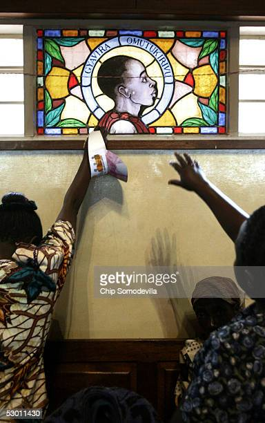 Christian pilgrims reach out to touch a stained glass window with the image of one of the Ugandan martyrs at the Catholic Basilica Church of the...