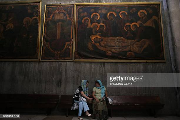 Christian pilgrims sit under a painting inside in the Greek Choir or Katholikon which is the central part of The Church of the Holy Sepulchre also...