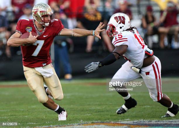 Christian Ponder of the Florida State Seminoles attempts to avoid the tackle of Culmer St Jean of the Wisconsin Badgers during the Champs Bowl on...