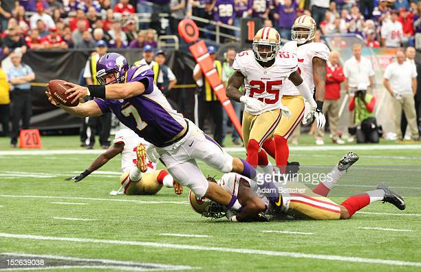 Christian Ponder of the Minnesota Vikings dives into the end zone during the second quarter while Ahmad Brooks of the San Francisco 49ers attempts...