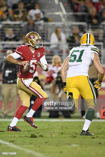 Christian Ponder of the San Francisco 49ers looks to get his pass off under pressure from outside linebacker Kyler Fackrell of the Green Bay Packers...