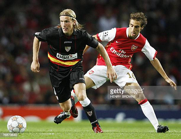 Christian Poulsen of Sevilla and Mathieu Flamini of Arsenal fight for the ball during a Champions League match at the Emirates Stadium in north...