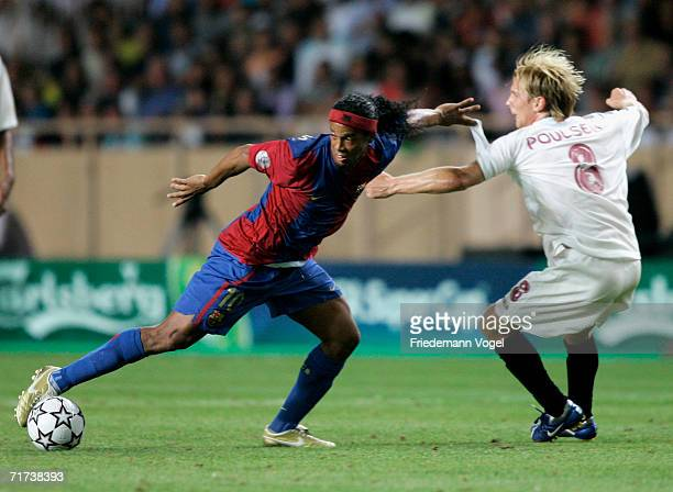 Christian Poulsen of Sevilla tussels for the ball with Ronaldinho of Barcelona during the UEFA Super Cup between FC Barcelona and FC Sevilla at the...