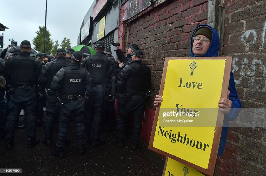 A christian protester with a 'Love Thy Neighbour' placard demonstrates as an Orange band are given a police escort as they pass the nationalist Ardoyne area during the Twelfth of July parade on July 13, 2015 in Belfast, Northern Ireland. The Ardoyne in Belfast has been a flashpoint for many years with both Catholics and Protestants involved in serious rioting and disturbances. The Twelfth is an Ulster Protestant celebration held annually. It celebrates the victory of Protestant king William of Orange over Catholic king James II at the Battle of the Boyne in 1690. This year the Twelfth takes place on the thirteenth of July due to the original date falling on a Sunday.