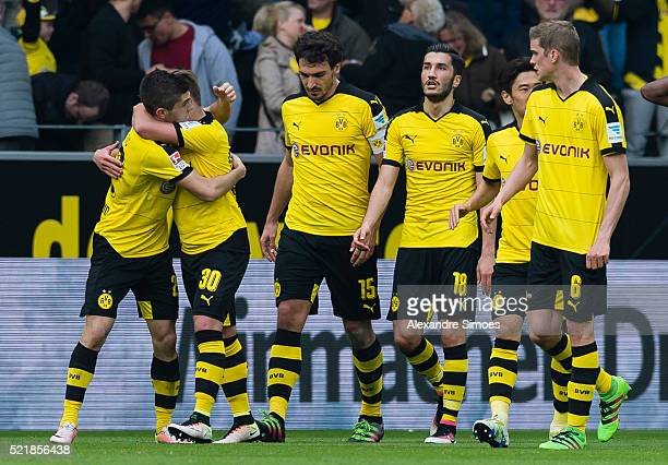 Christian Pulisic of Borussia Dortmund celebrates after scoring the opening goal together with his team mates during the Bundesliga match between...
