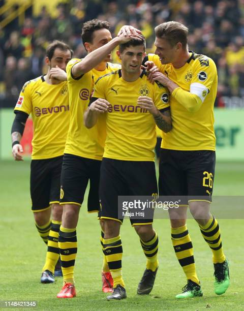 Christian Pulisic of Borussia Dortmund celebrates with teammates after scoring his team's first goal during the Bundesliga match between Borussia...