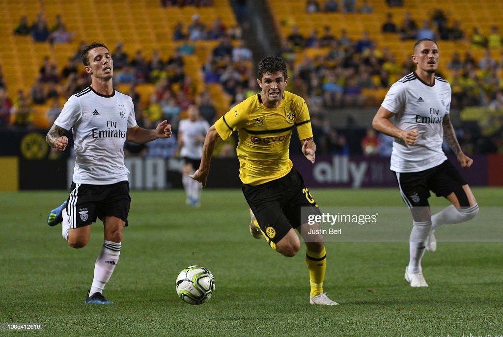 Christian Pulisic #22 of Borussia Dortmund controls the ball as he runs past Alex Grimaldo #3 and Ljubomir Fejsa #5 of Benfica in the first half during the 2018 International Champions Cup match at Heinz Field on July 25, 2018 in Pittsburgh, Pennsylvania.