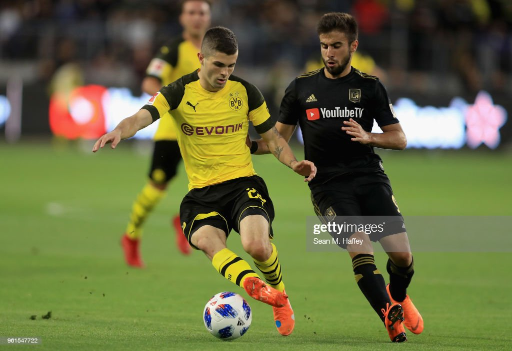Christian Pulisic #22 of Borussia Dortmund dribbles past Diego Rossi #9 of Los Angeles FC during the first half of an International friendly soccer match at Banc of California Stadium on May 22, 2018 in Los Angeles, California.
