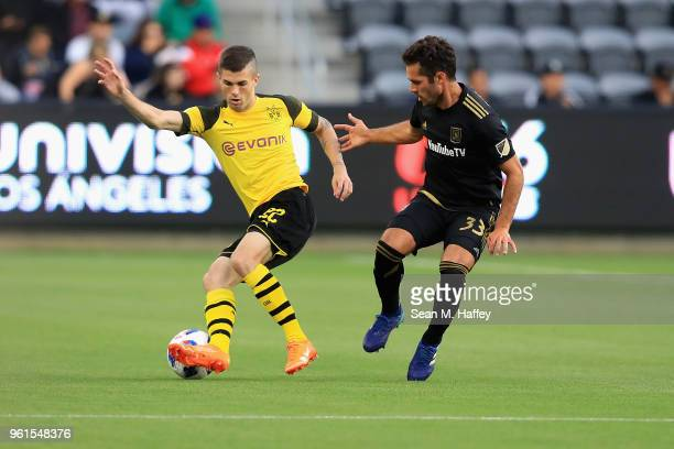 Christian Pulisic of Borussia Dortmund dribbles past Julian Weigl of Borussia Dortmund during the first half of an International friendly soccer...