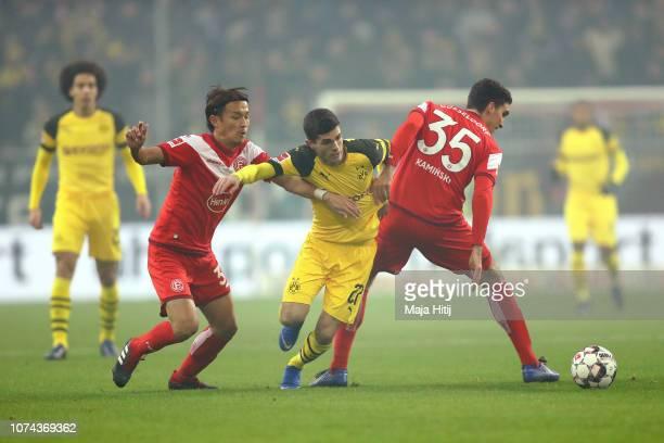 Christian Pulisic of Borussia Dortmund is challenged by Takashi Usami of Fortuna Duesseldorf and Marcin Kaminski of Fortuna Duesseldorf during the...