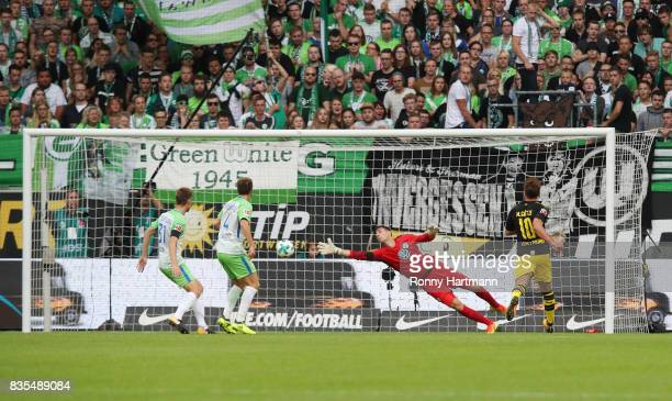 Christian Pulisic of Borussia Dortmund scores the first goal of the match while Mario Goetze of Borussia Dortmund looks on and goalkeeper Koen...