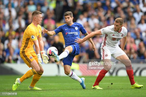 Christian Pulisic of Chelsea attempts to take the ball past Dean Henderson of Sheffield United as he is challenged by Jack O'Connell during the...