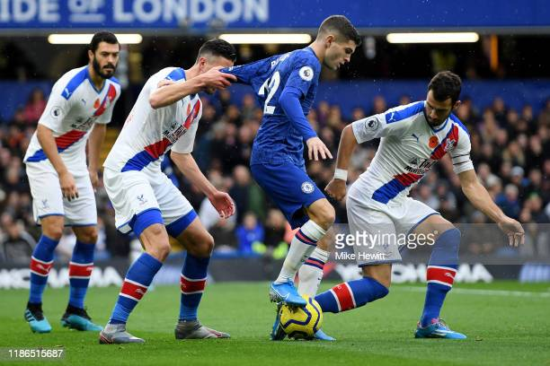 Christian Pulisic of Chelsea is challenged by James Tomkins Sam Woods and Luka Milivojevic of Crystal Palace during the Premier League match between...