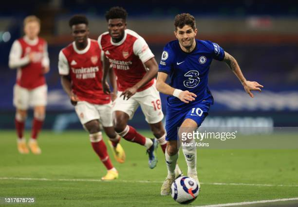 Christian Pulisic of Chelsea runs to keep the ball in play under pressure from Thomas Partey of Arsenal during the Premier League match between...