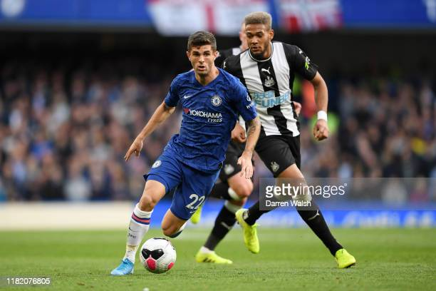 Christian Pulisic of Chelsea runs with the ball under pressure from Joelinton of Newcastle United during the Premier League match between Chelsea FC...