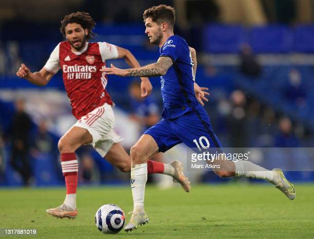 Christian Pulisic of Chelsea runs with the ball under pressure from Mohamed Elneny of Arsenal during the Premier League match between Chelsea and...