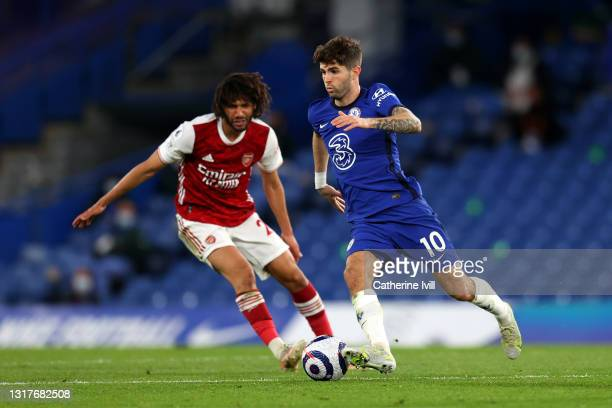Christian Pulisic of Chelsea runs with the ball whilst under pressure from Mohamed Elneny of Arsenal during the Premier League match between Chelsea...