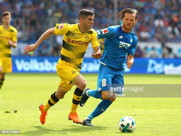 Christian Pulisic of Dortmund and Eugen Polanski of Hoffenheim battle for the ball during the Bundesliga match between TSG 1899 Hoffenheim and...