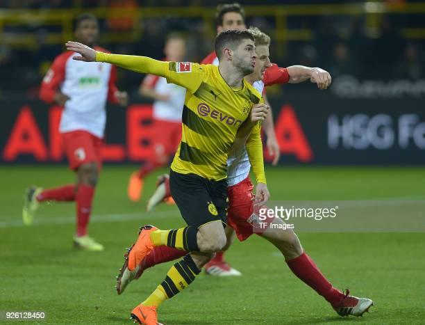 Christian Pulisic of Dortmund and Martin Hinteregger of Augsburg battle for the ball during the German Bundesliga match between Borussia Dortmund v...
