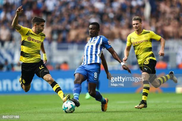 Christian Pulisic of Dortmund and Salomon Kalou of Berlin battle for the ball during the Bundesliga match between Borussia Dortmund and Hertha BSC at...