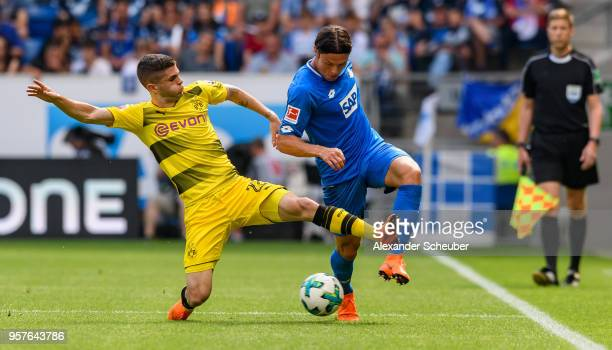 Christian Pulisic of Dortmund challenges Nico Schulz of Hoffenheim during the Bundesliga match between TSG 1899 Hoffenheim and Borussia Dortmund at...